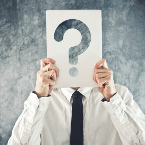 Businessman holding paper with printed question mark in front of his face